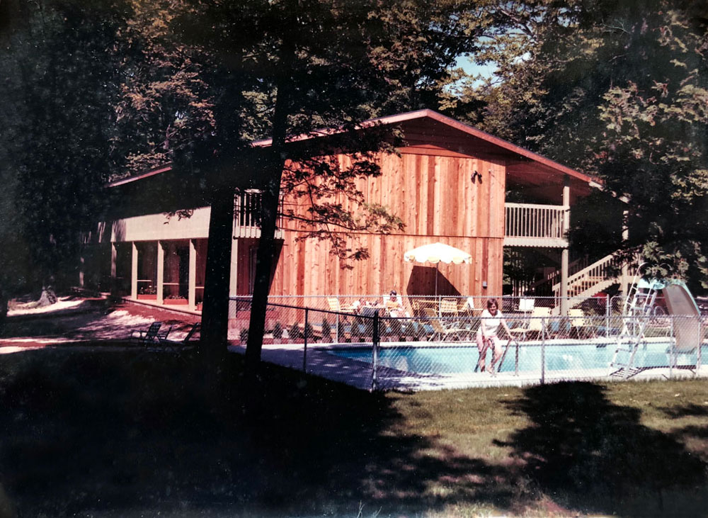 Exterior of Shallows motel and pool with guests from 1960s