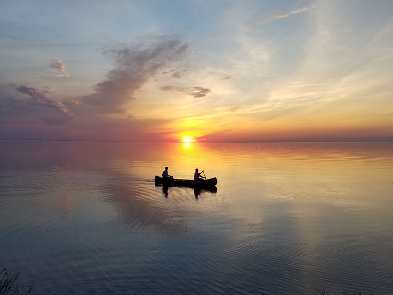 Two people canoeing across lake as sun sets