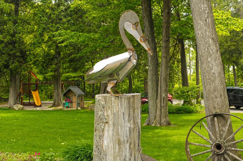 Metal pelican sculpture on wooden base