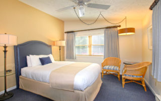 Woodview room interior with large bed, chairs and windows