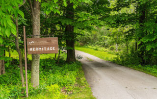 Wooden sign for Hermitage along wooded driveway