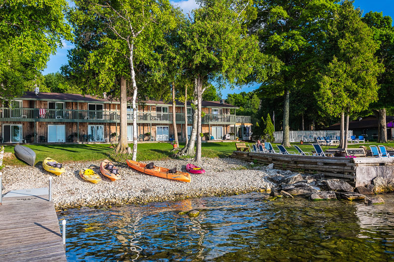 Several kayaks along the waters edge with the shoreside motel in the Background