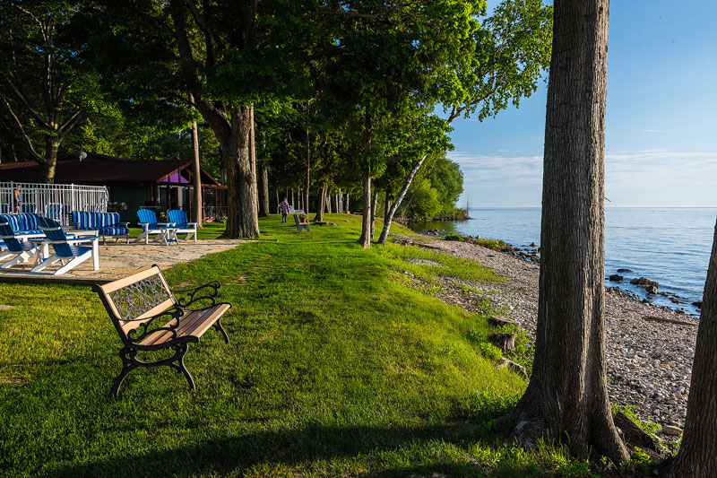 Stone patio, chairs and bench along the shoreline of the bay