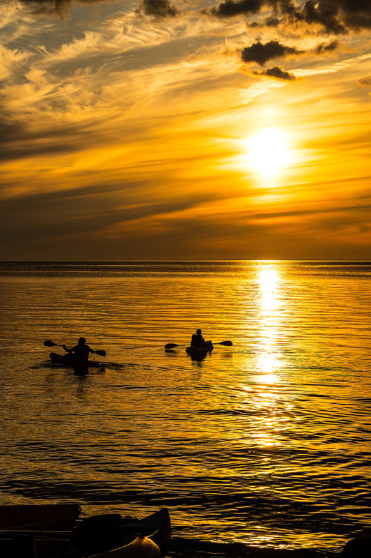 Two kayakers at sunset on the bay