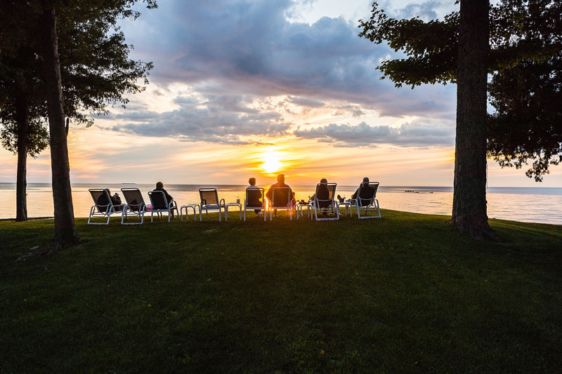 Group of people sitting on deck chairs watching the sun set over the bay