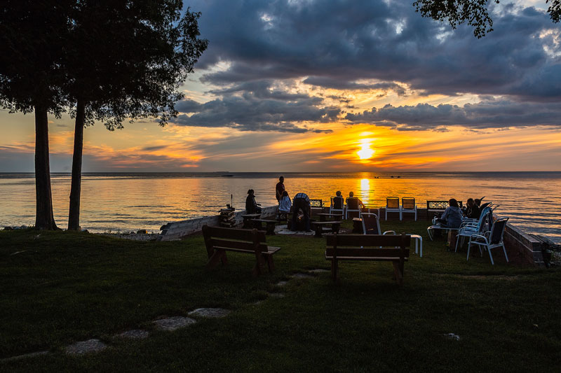 Gathering of people watching colorful sunset from patio overlooking the bay