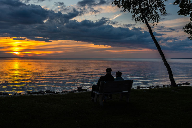 Resort guests relaxing on bench by the water at sunset