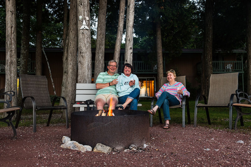 Three guests enjoying the firepit