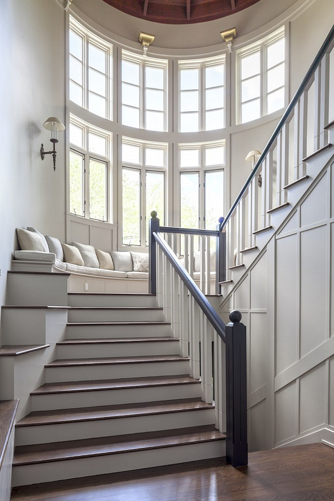 Staircase with large windows and a bench sitting area