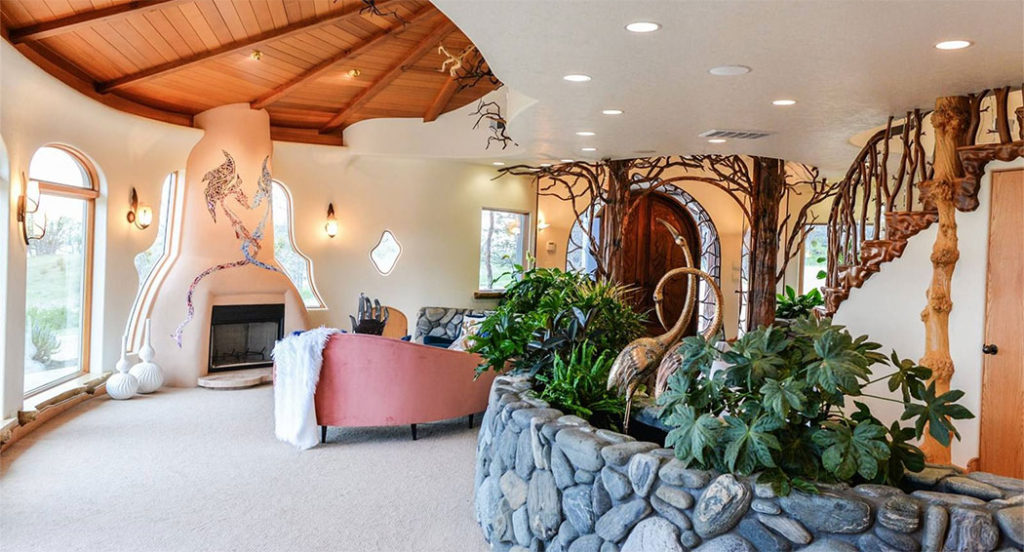 The living room has a grand, adobe-inspired wood-burning fireplace with a glass mosaic inlay of two intertwined dragons intertwined.