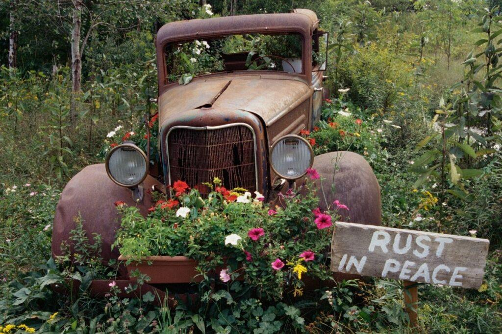 Vintage car turned into a planter with Rust in Peace sign