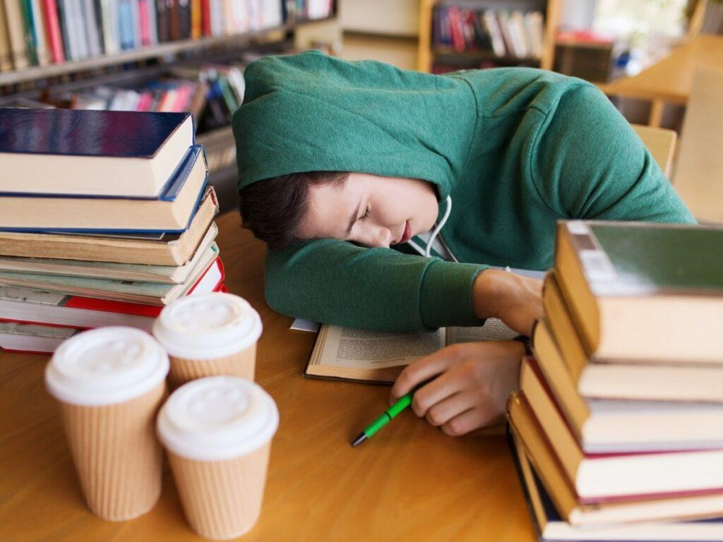 Tired College Student Asleep on a Stack of Books