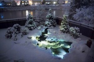 glowing pond surrounded by heavy blankets of snow