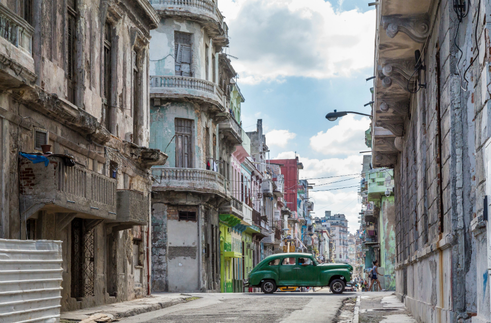 the streets of old havana with a green car running through it
