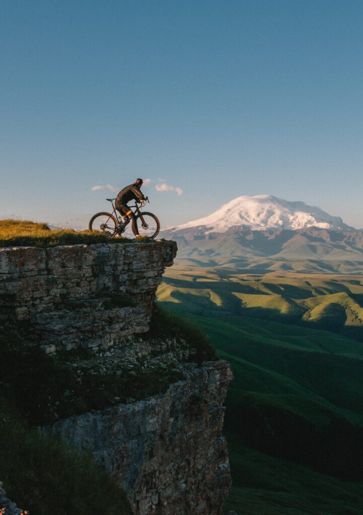Biker on the edge of a cliff overlooking a beautiful view