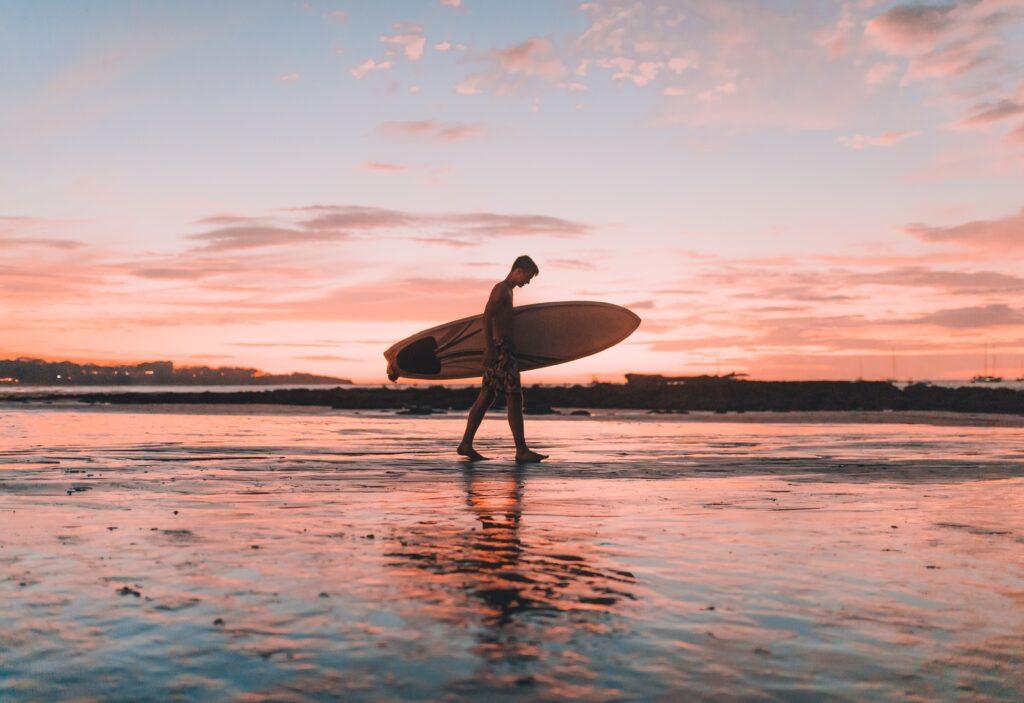 Boy walking with surfboard