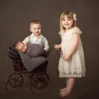 Newborn photography - baby in buggy with toddler siblings