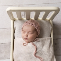 Photo of newborn girl in bed prop