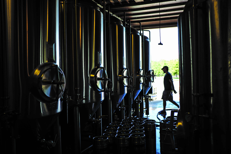 Head Brewer Kurt Krol walks by the brewery's 13 fermentation vessels.