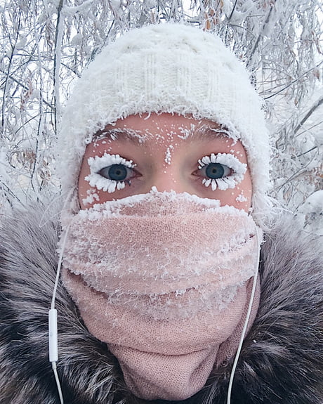 A person with frost across a face covering and heavily layered on their eyelashe