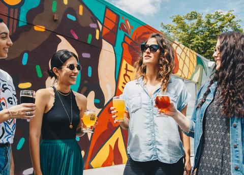 women consuming cannabis outside this spring with cocktails