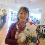 Woman holding white dog in Santa hat