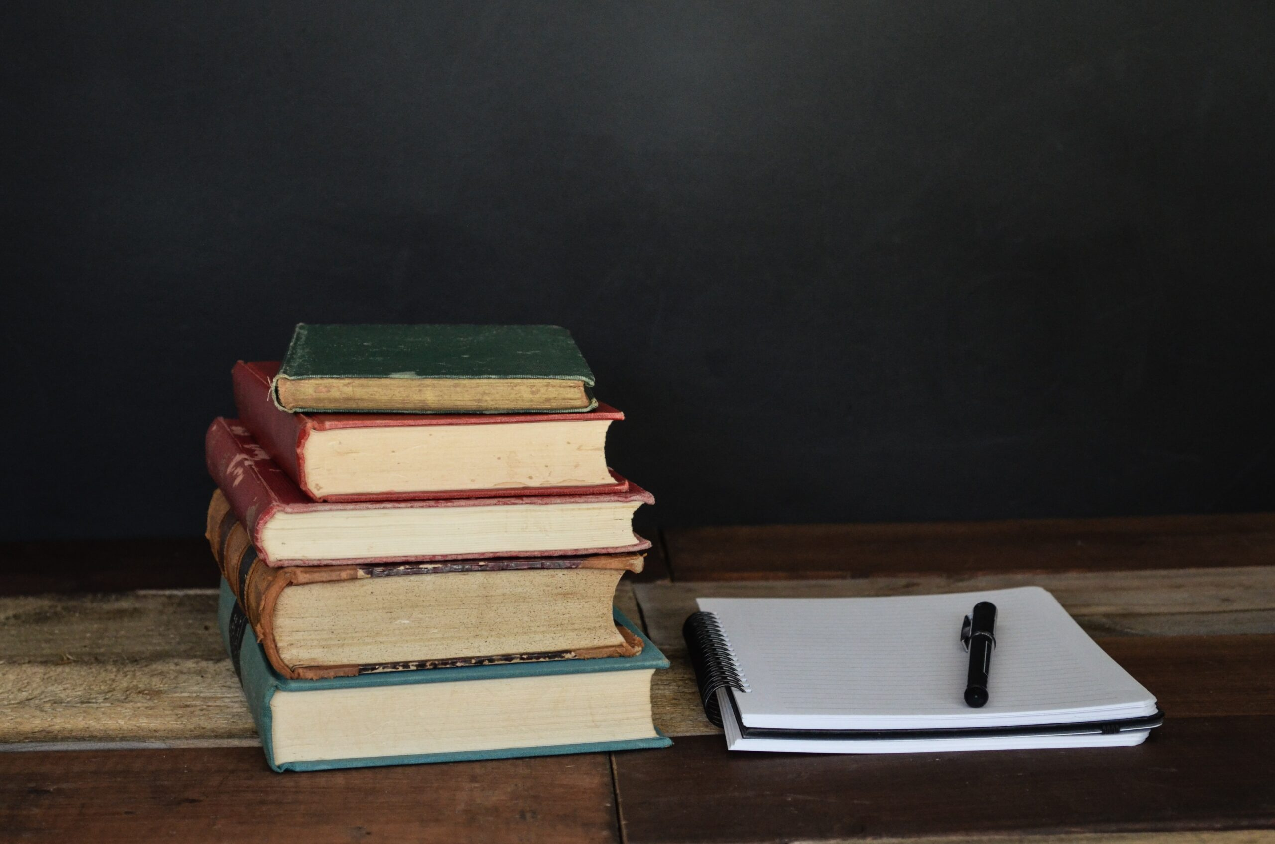 Stack of Books next to a notepad and pen