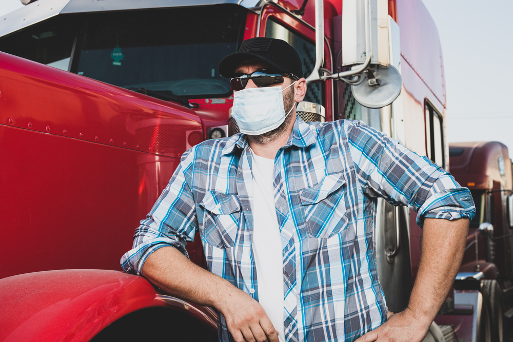 CDL truck driver standing in front of a truck wearing a mask