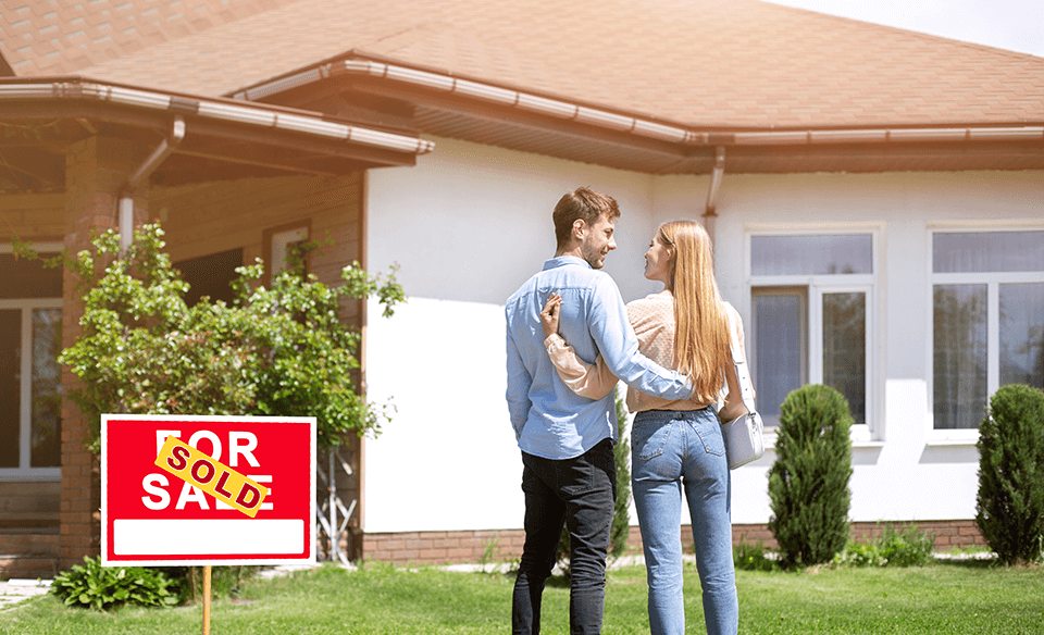 Couple stands in front of their new house after having their credit repaired.