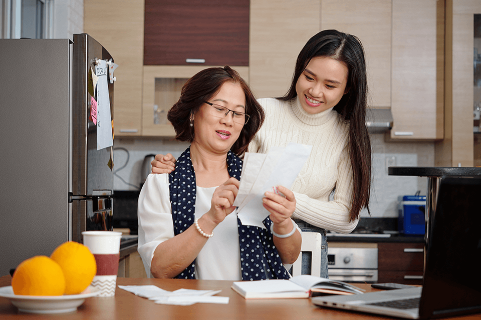 Mother and daughter paying bills after debt consolidation.