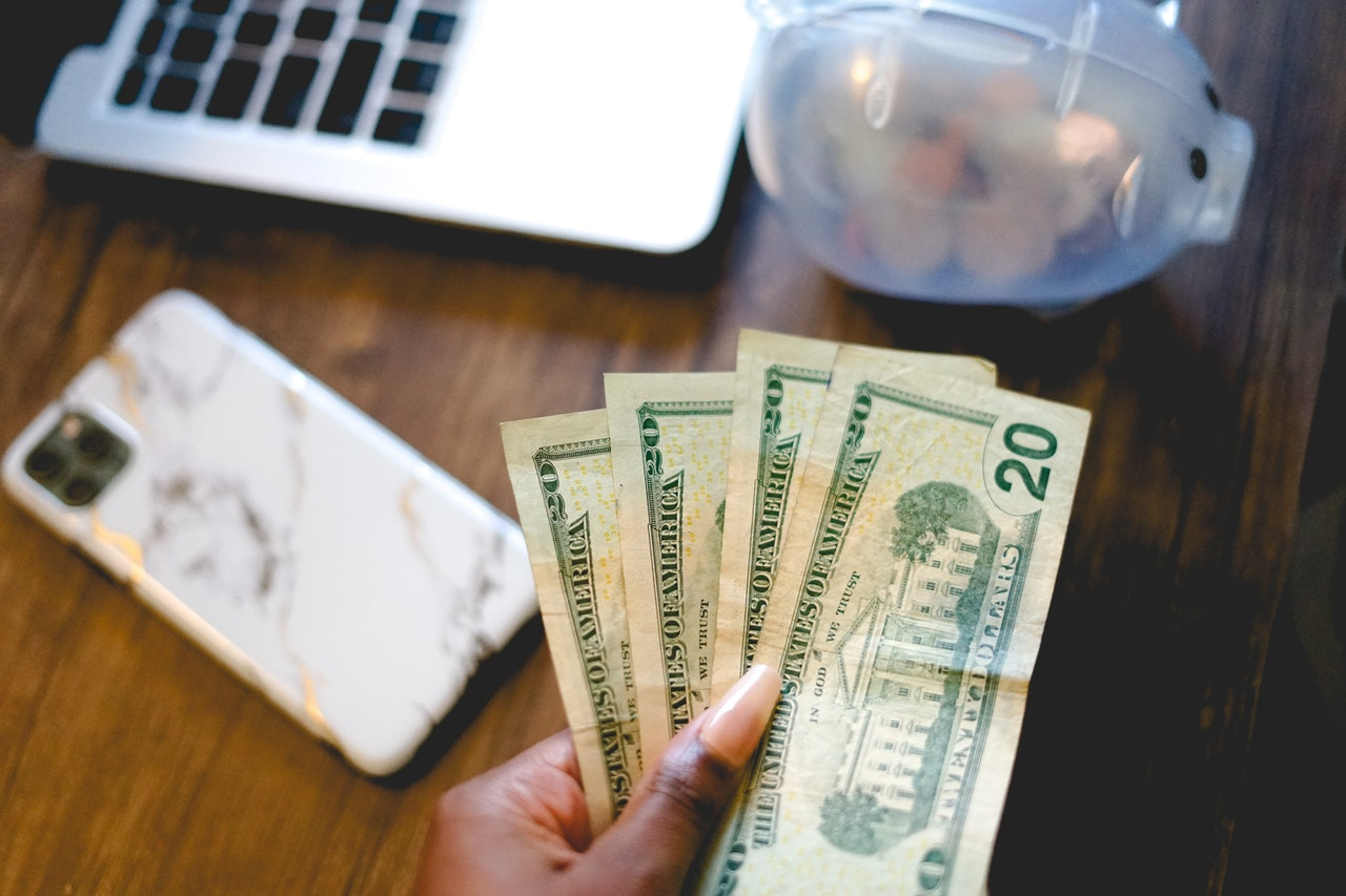 A Black woman's hand is shown holding money. A computer sits in the background.