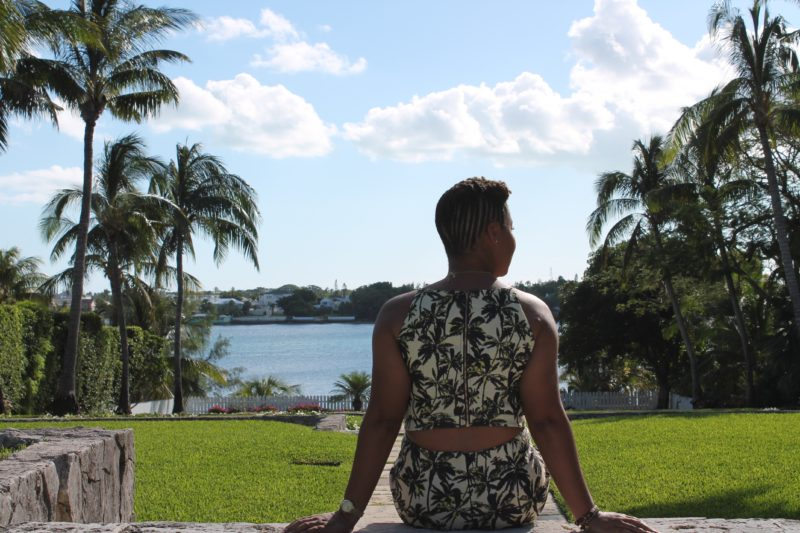 This Bahamian Gyal blogger, Rogan Smith sits on steps with her back turned to the camera at the French Cloisters on Paradise Island in The Bahamas