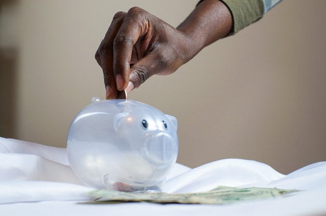 Photo of a black hand putting coins inside of a clear piggybank