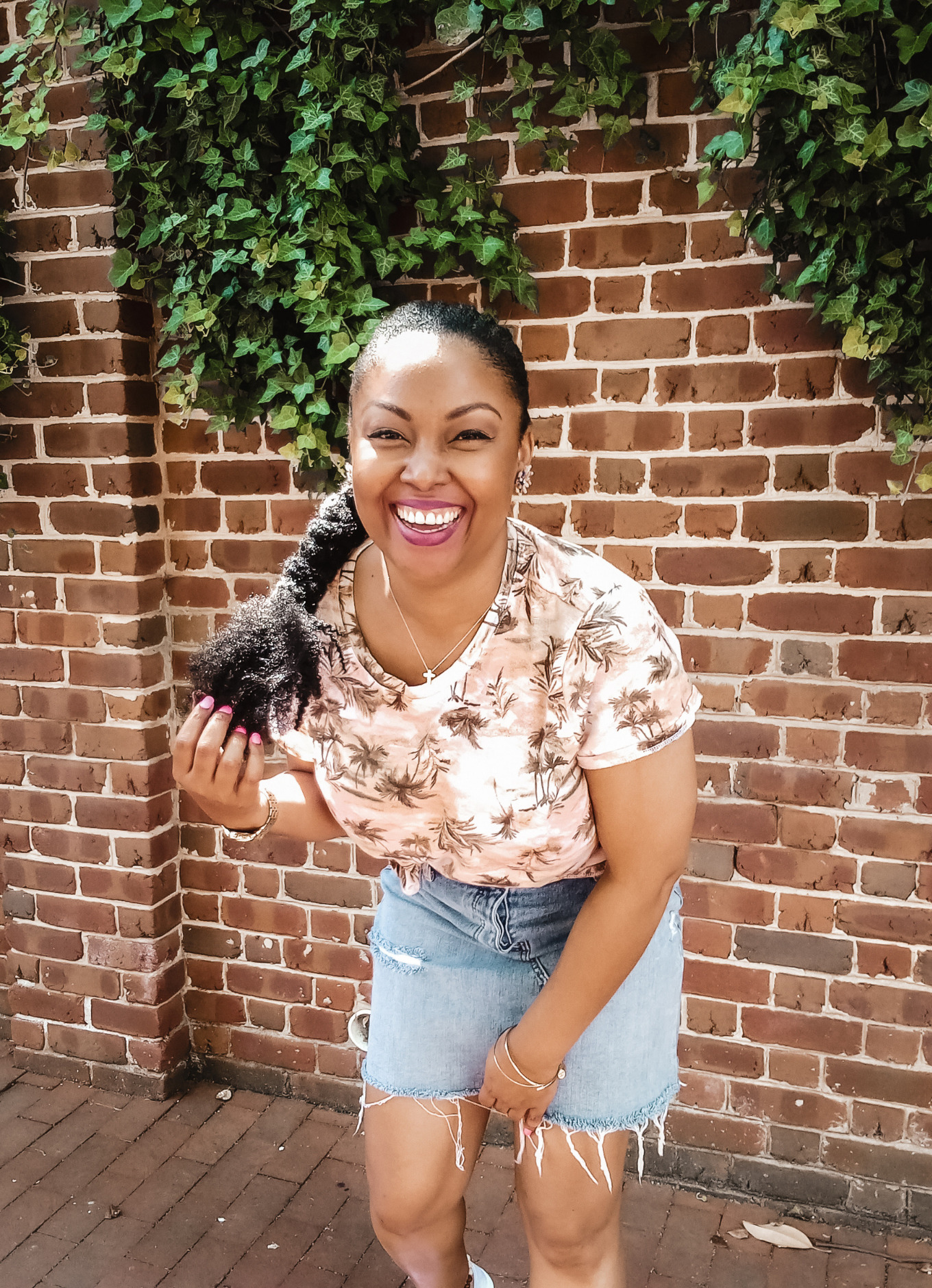 Washington DC-based blogger, Rogan Smith smiles and poses in front of a brick wall in Georgetown, DC