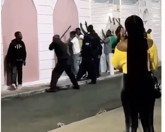 Royal Bahamas Police Force officers line a group of young men up against a wall and beat them with batons.