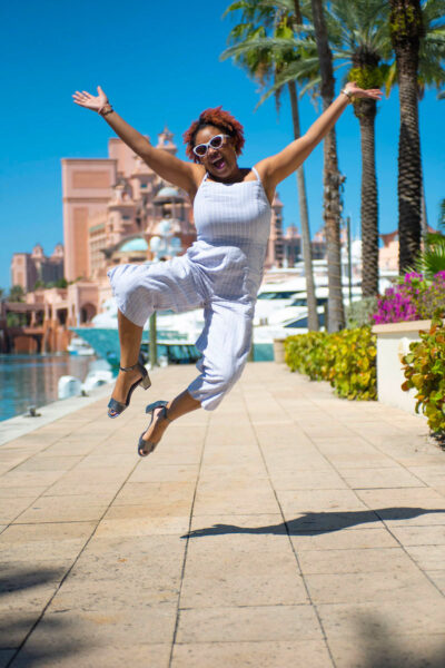 This Bahamian Gyal blogger and Creative Director, Rogan Smith jumps for joy in Marina Village at the Atlantis Paradise Island resort in The Bahamas. The Bahamas will open for travel on July 1.
