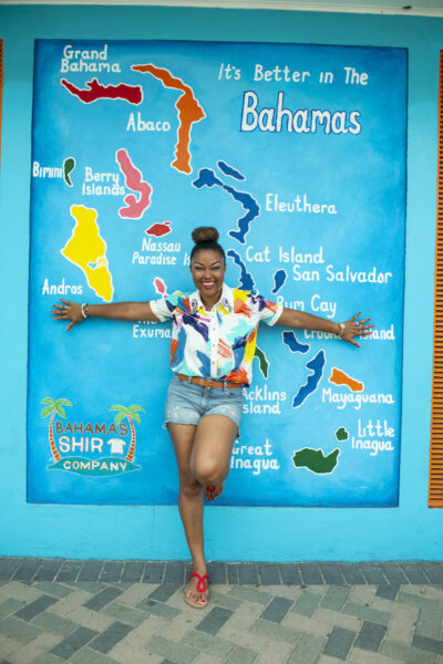 """This Bahamian Gyal blogger, Rogan Smith poses in front of a painted mural that states, """"It's Better In The Bahamas."""" The Bahamas reopens for travel on Wednesday. (Photo/T. Glinton Photography)"""