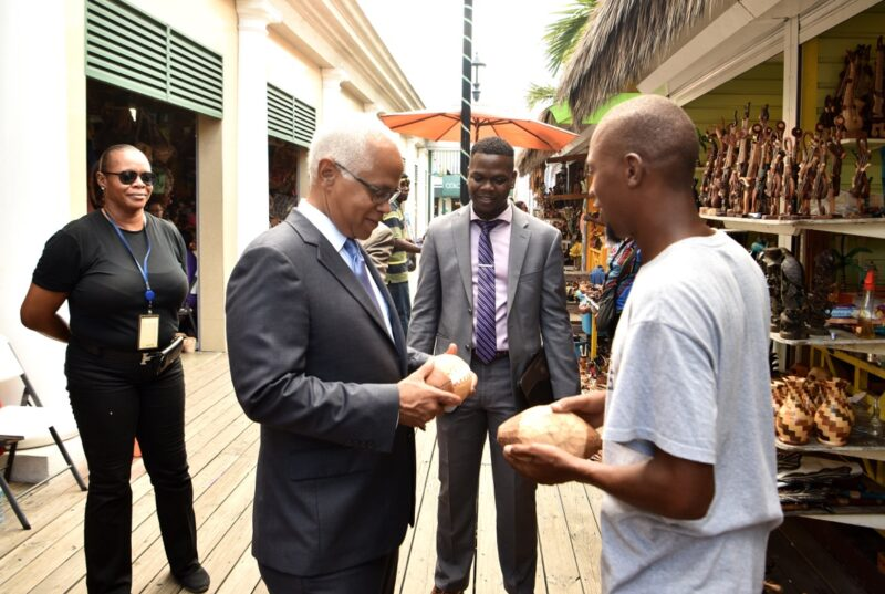 Travis Robinson (centre) looks on as Tourism Minister, Dionisio D'Aguilar inspects souvenirs at the Straw Market in Nassau, Bahamas.