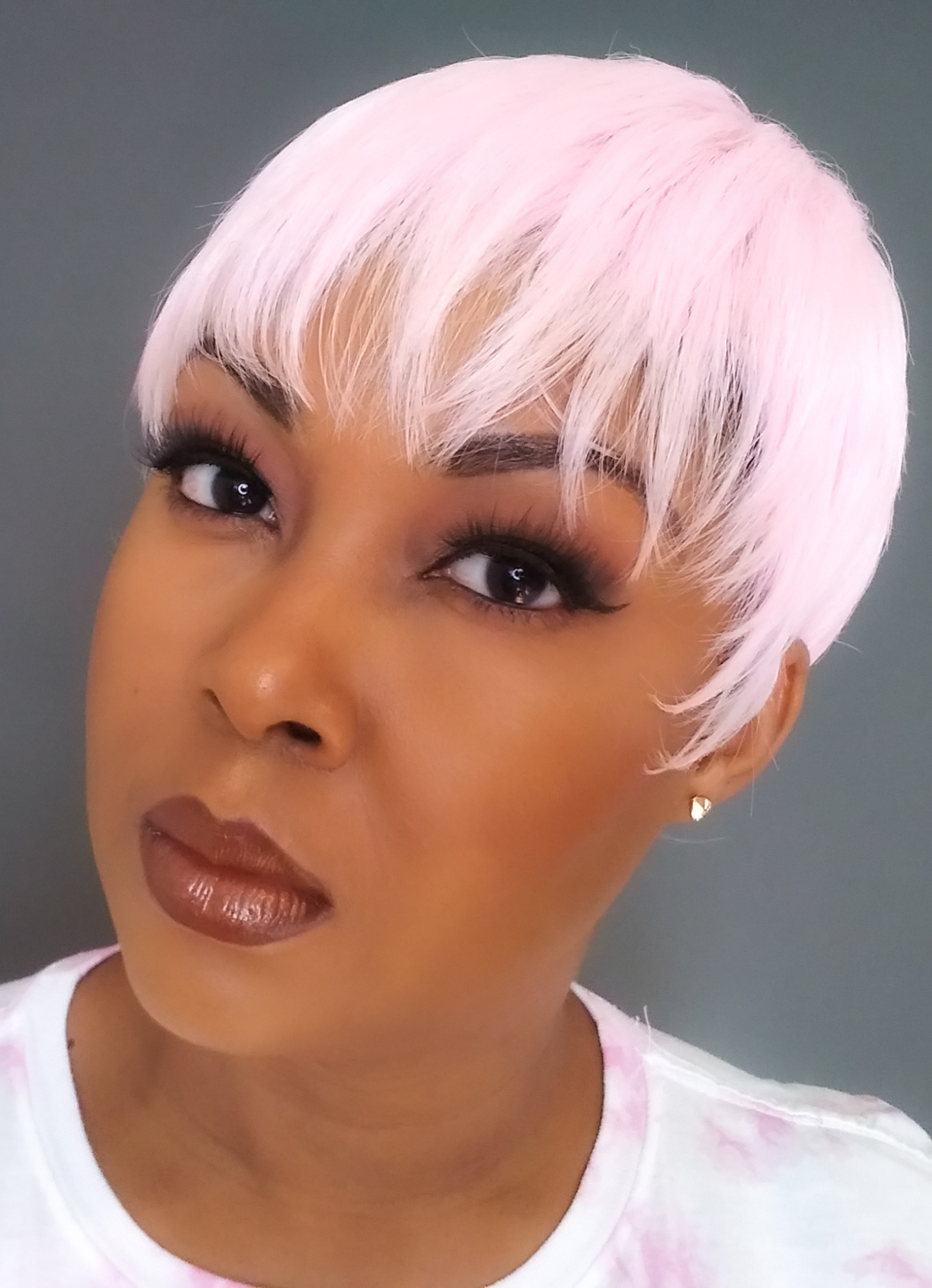 light skinned black woman wearing pink pixie wig