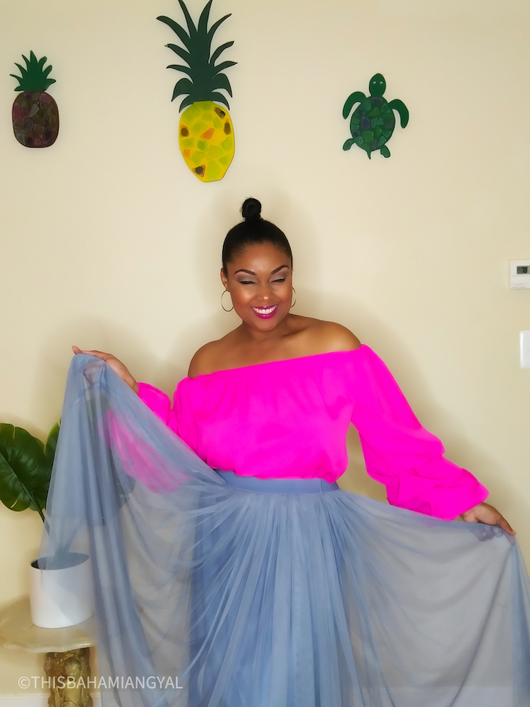 Black woman wears a pink off the-shoulder blouse with a flow skirt.