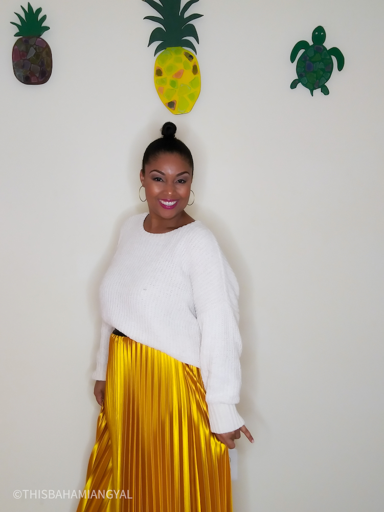Beauty and lifestyle blogger, Rogan Smith wears a mustard-yellow satin midi skirt with a cream-coloured sweater.
