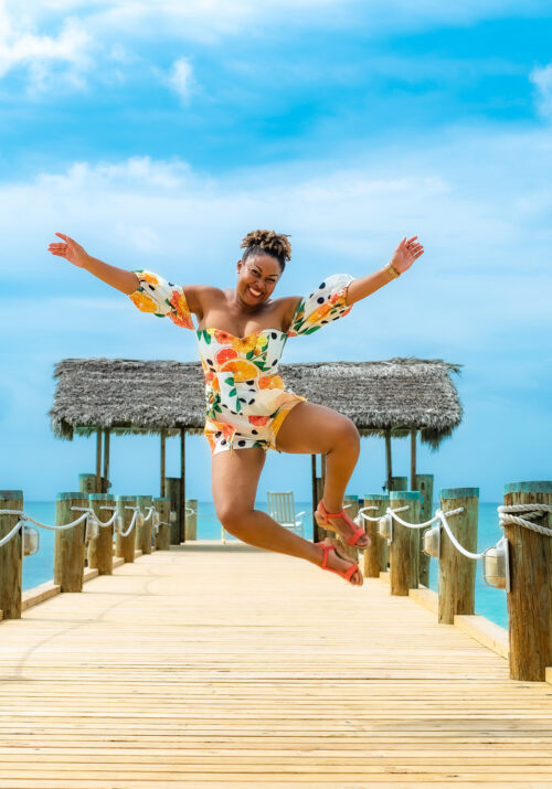 This Bahamian Gyal blogger, Rogan Smith jumps in the air with her hands outstretched. She is on a dock with the gorgeous blue ocean and sky behind her