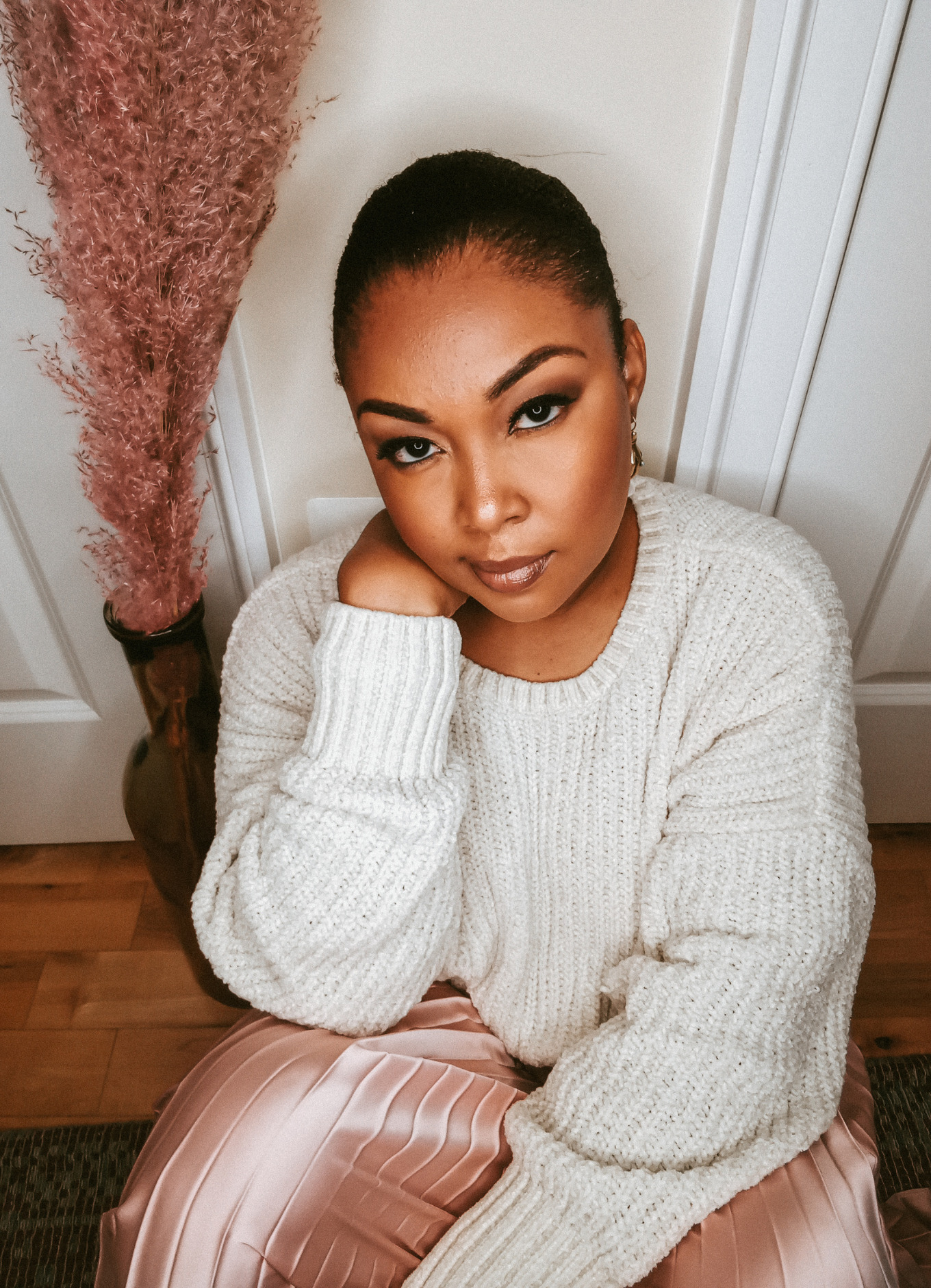 Black woman wearing pink skirt and white sweater sits on the ground looking somber.