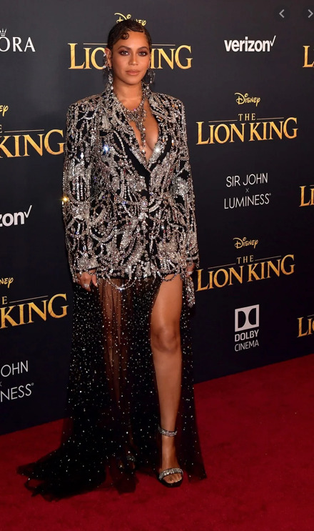 Beyonce at Disney's The Lion King premiere. She poses in front of a sign for The Lion King.