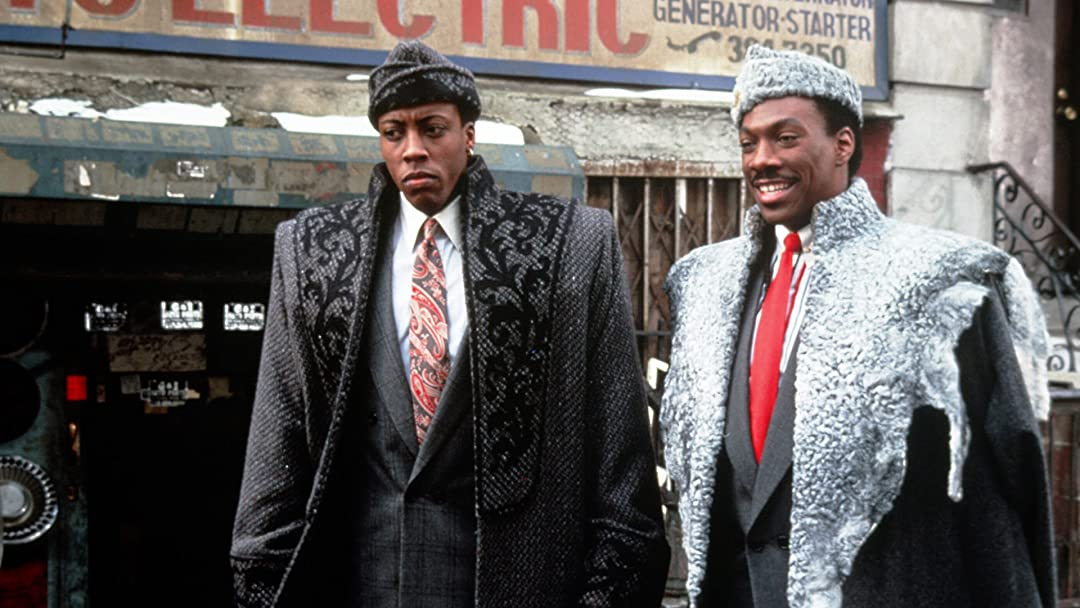 Original still shot from the iconic Coming To America. Arsenio Hall and Eddie Murphy pose in a picture.