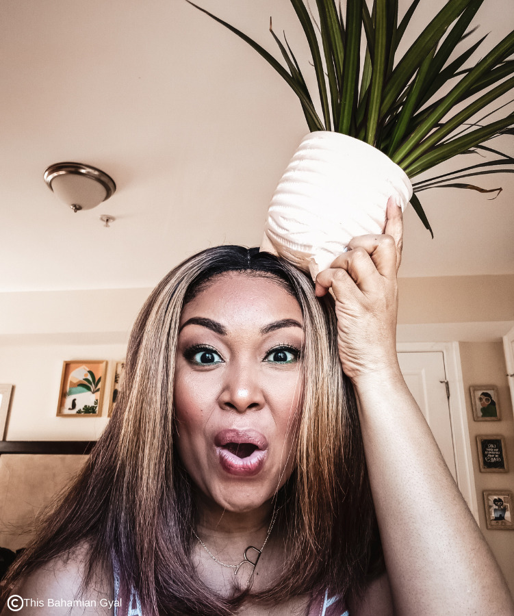 Black woman holds plants on her head