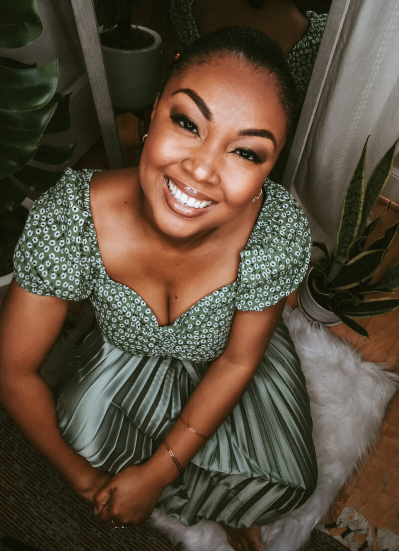 Black female blogger sits on ground and smiles at camera