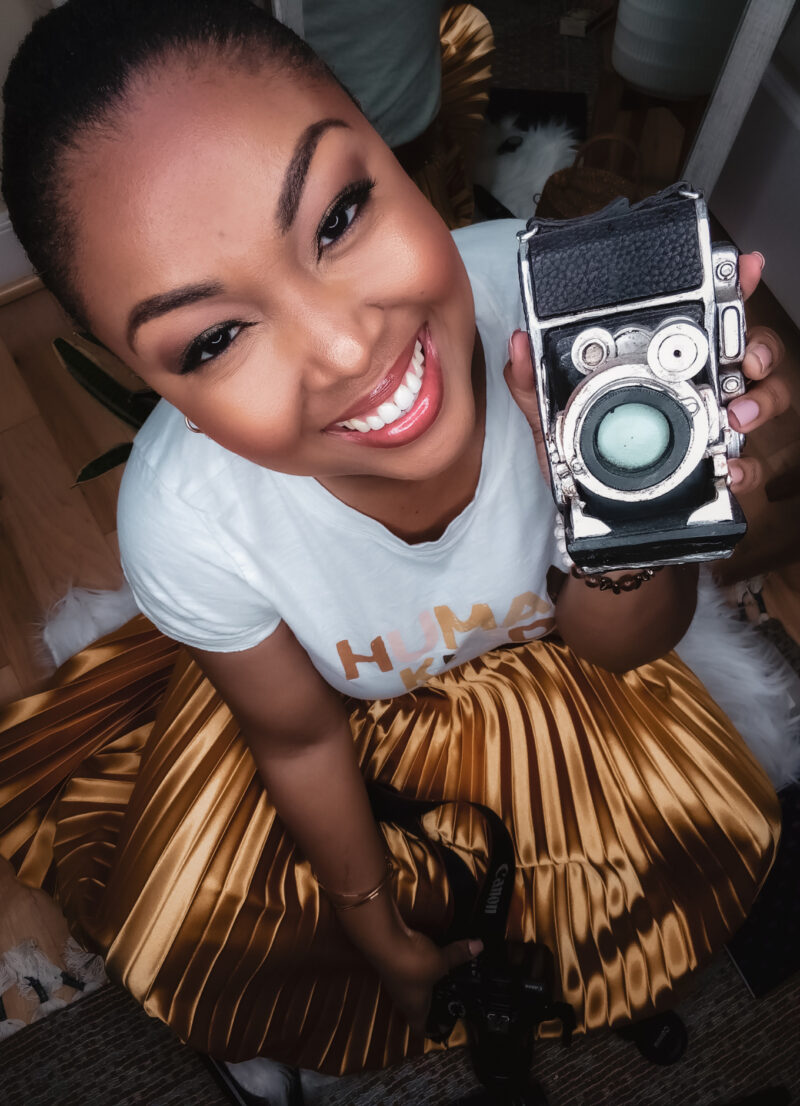 Washington DC blogger Rogan Smith poses for the camera holding a vintage camera replica