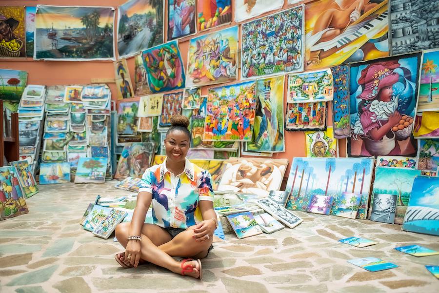 Blogger Rogan sits among artwork in Nassau, Bahamas