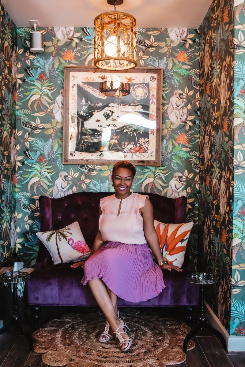 Blogger and content producer, Rogan sits on the velvet purple chair in Bon Vivants in Sandyport, Nassau, Bahamas
